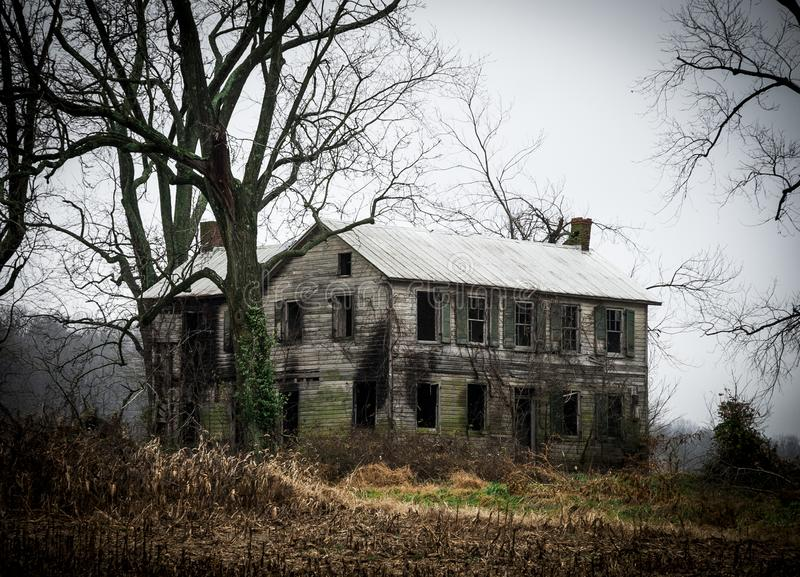 沿车行道的被放弃的农舍房子 库存照片