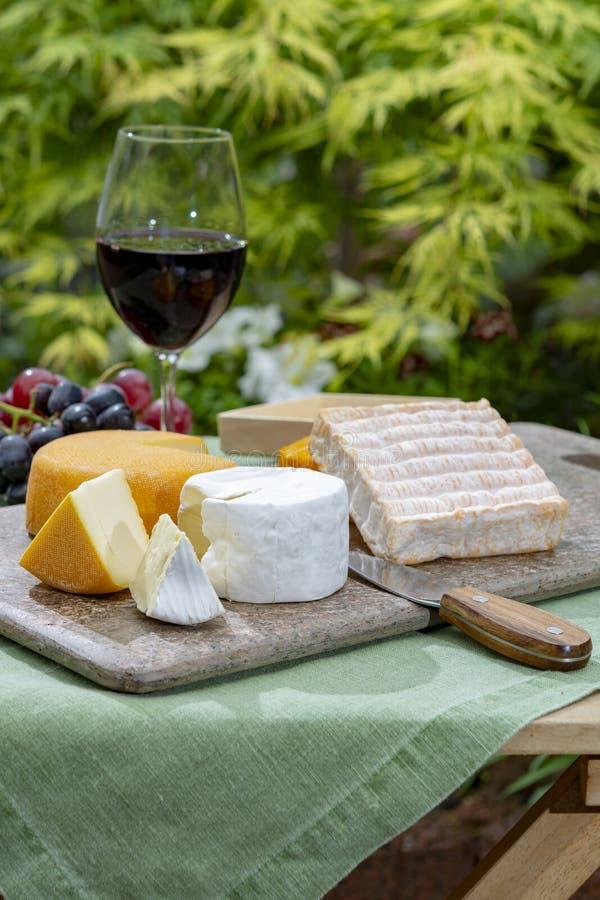 法国乳酪收藏、黄色Riche de Saveurs,Vieux单块玻璃和Le peche des好的妙语佩雷斯乳酪服务与杯红色口岸 库存照片