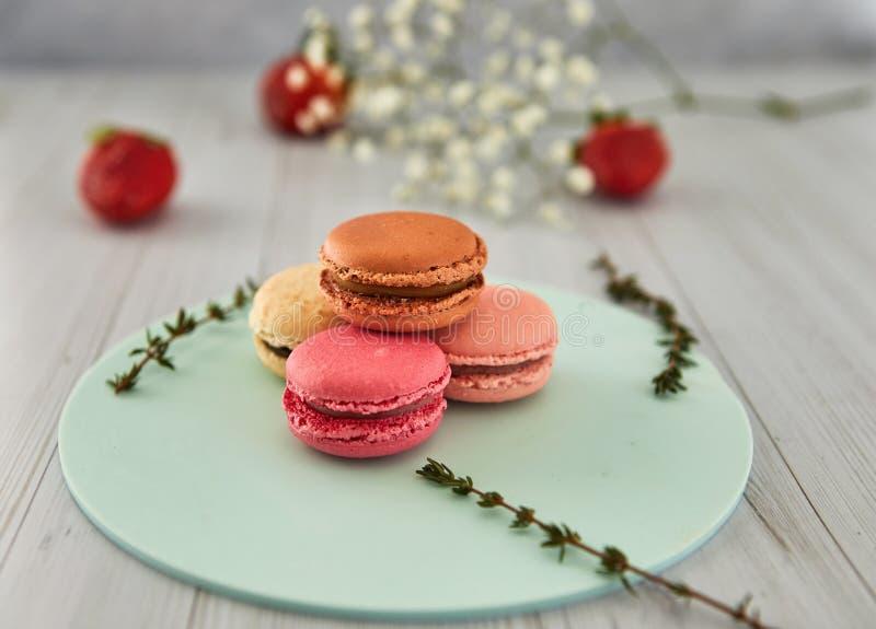 法国五颜六色的蛋白杏仁饼干 在轻的背景的五颜六色的淡色蛋白杏仁饼干用新鲜的草莓 库存照片