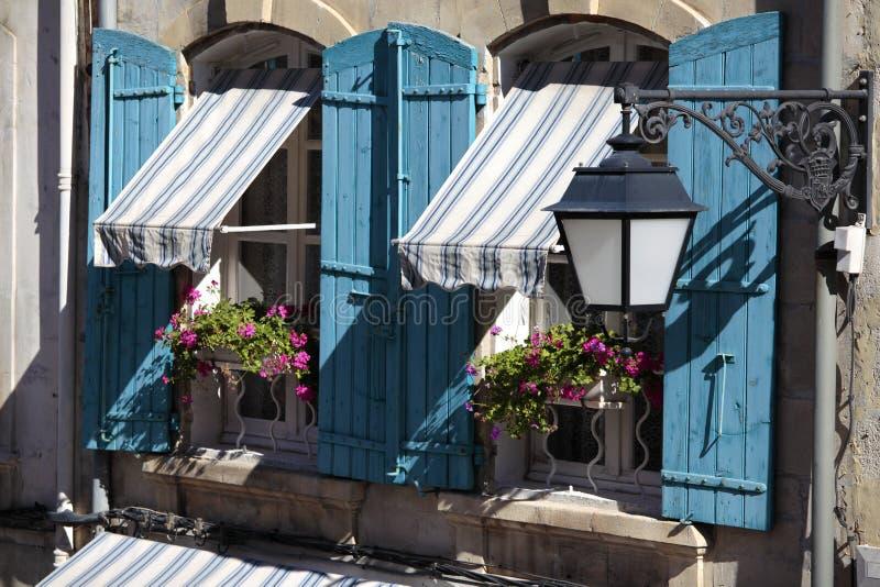 法国南普罗旺斯样式村庄窗口、蓝色快门和花箱子 免版税库存照片