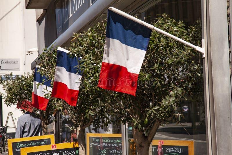 法国咖啡馆大阳台飞行在餐馆和商店前面的三颜色 与椅子、桌、billbords和橄榄色的t的外部图象 免版税库存图片