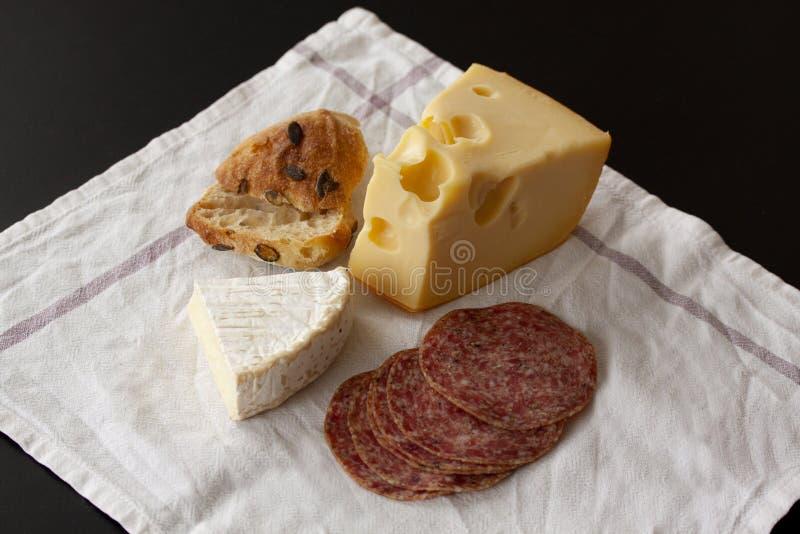 法国咸味干乳酪和瑞士瑞士干酪乳酪与在白色餐巾背景安置的切片蒜味咸腊肠香肠和一个家庭焙制的小圆面包 免版税库存图片