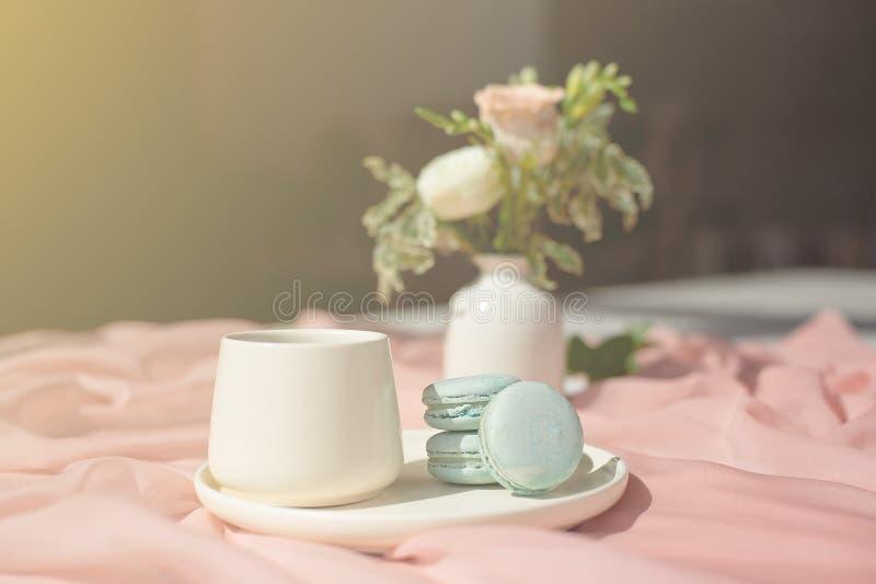 法国在桃红色和咖啡杯身分的蛋白杏仁饼干蓝色板材在与桃红色桌布白色花瓶的一张木桌上与 库存图片