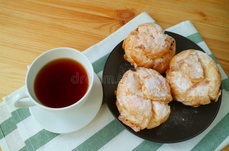 法国奶油泡芙或州板材与在木表上热的茶供食的一杯的la奶油 库存图片