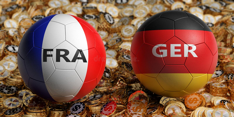 法国对 德国足球比赛-在法国和德国全国颜色的足球在金黄美元硬币床上  免版税图库摄影