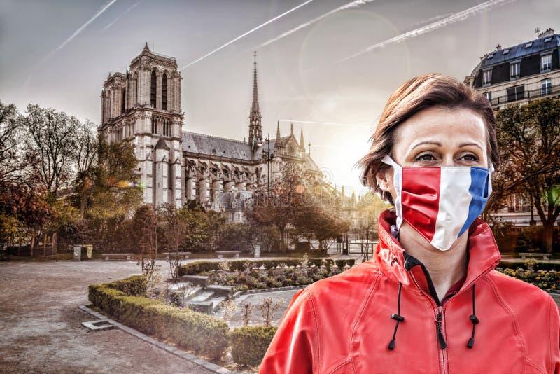 法国巴黎圣母院日出时戴法国国旗保护面罩防冠状病毒 免版税库存照片