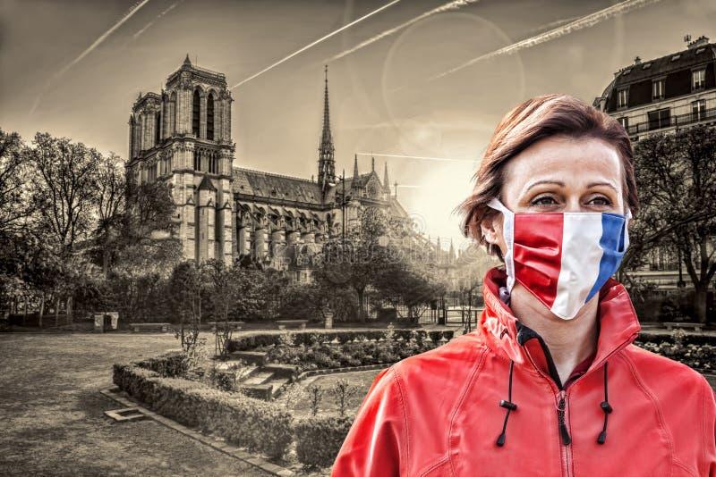 法国巴黎圣母院日出时戴法国国旗保护面罩防冠状病毒 库存图片