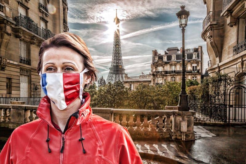 法国巴黎埃菲尔铁塔前戴有法国国旗防冠状病毒防护面罩的女子 库存图片