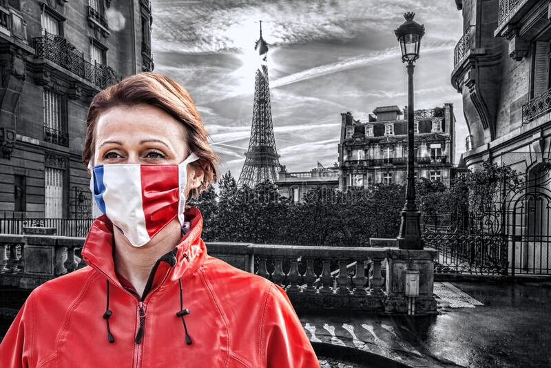 法国巴黎埃菲尔铁塔前戴有法国国旗防冠状病毒防护面罩的女子 免版税库存照片