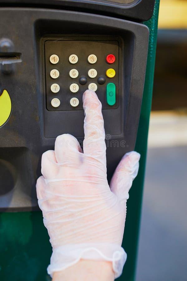 法国巴黎街上的女手戴保护性单用手套按停车仪表按钮 库存照片