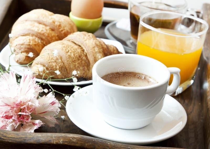 法国早餐用咖啡、花和新月形面包 免版税图库摄影