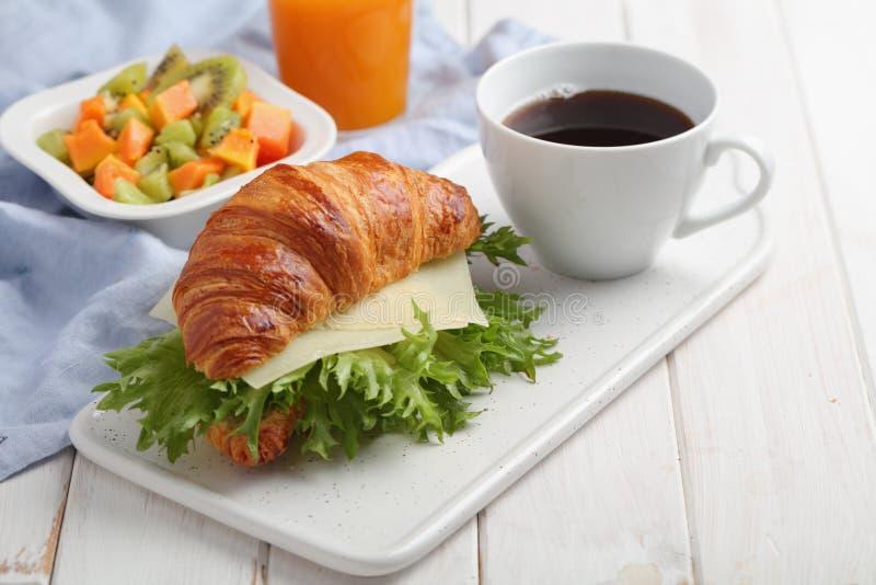 法国早餐:新月形面包三明治用乳酪、水果沙拉和咖啡 免版税库存图片