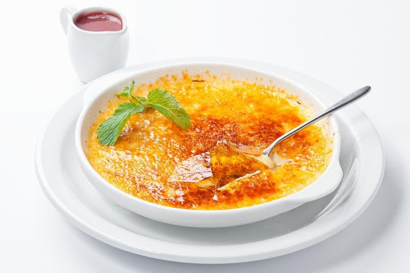 法国点心焦糖奶油用莓果调味汁和薄菏 库存照片