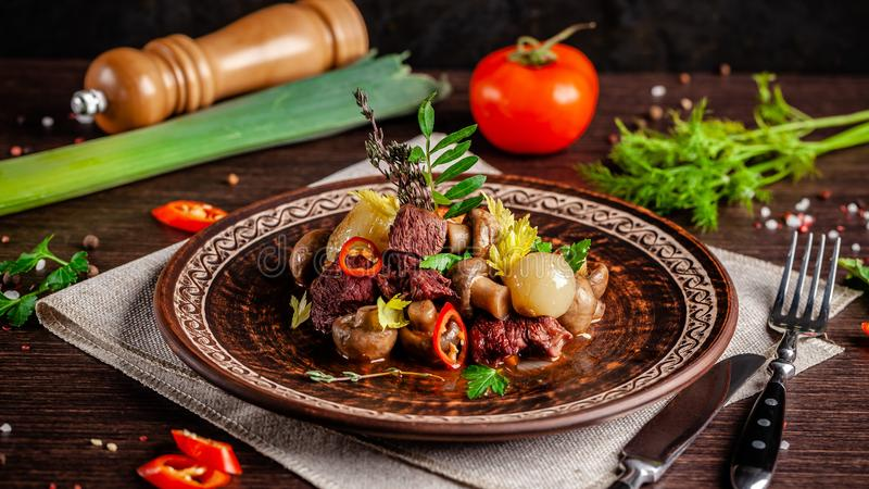 法国烹调概念 小牛肉blanquette用蘑菇、整个被炖的葱、红萝卜和辣椒 大盘子 免版税库存照片