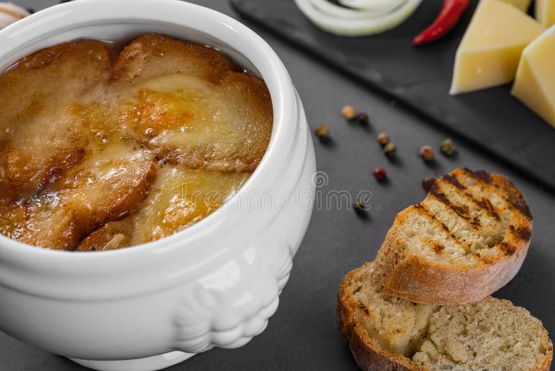 法国葱乳酪汤用油煎方型小面包片 服务在灰色背景的一个白色罐 免版税库存图片