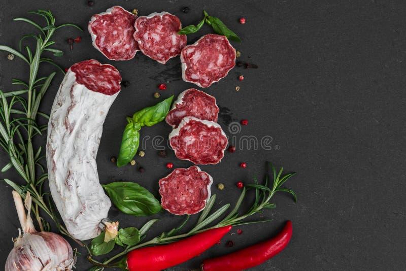 法国蒜味咸腊肠用迷迭香、大蒜、辣椒和干胡椒在黑板岩背景 与拷贝空间的顶视图 免版税库存图片