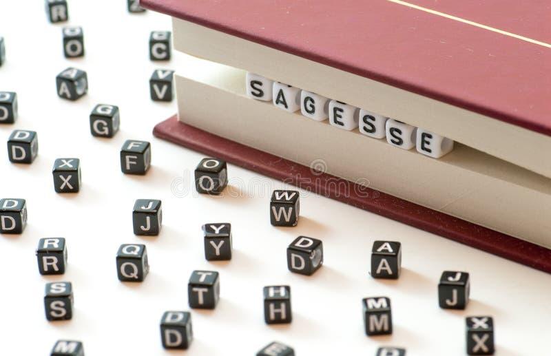 法国词sagesse意思智慧写与信件被困住在书归档和在白色背景concep的传播信件之间 库存图片