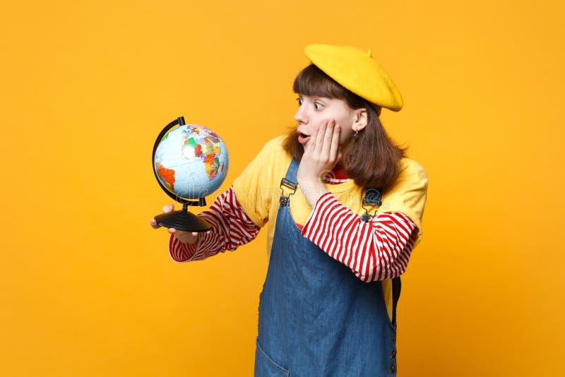 法国贝雷帽和牛仔布sundress的震惊女孩少年在拿着地球世界地球的面颊上在黄色把手放被隔绝 库存照片