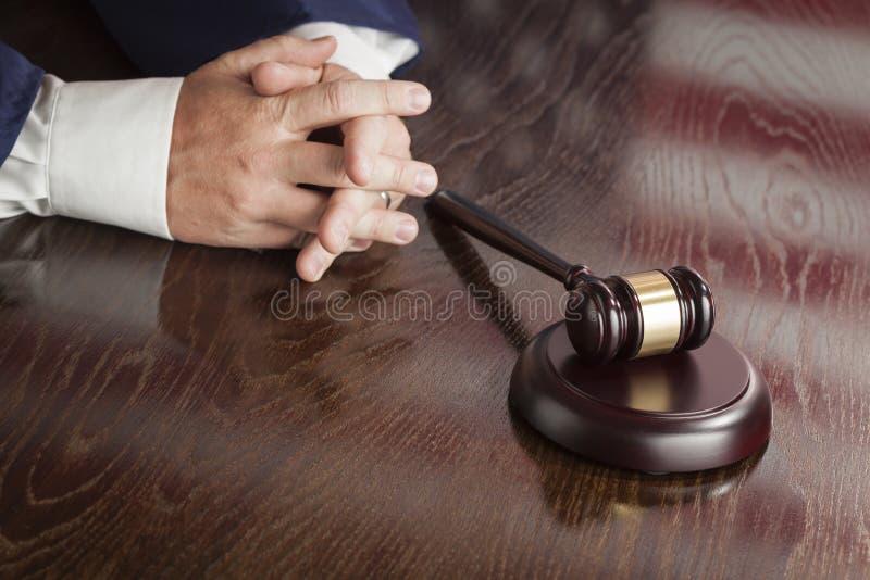 法官休息在惊堂木后的手有美国国旗表的Reflecti 免版税库存照片