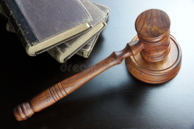 法官惊堂木和旧书在黑木表上 免版税图库摄影