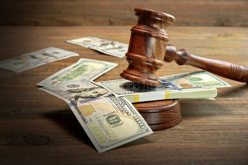 法官或拍卖人惊堂木和金钱在木表上 图库摄影