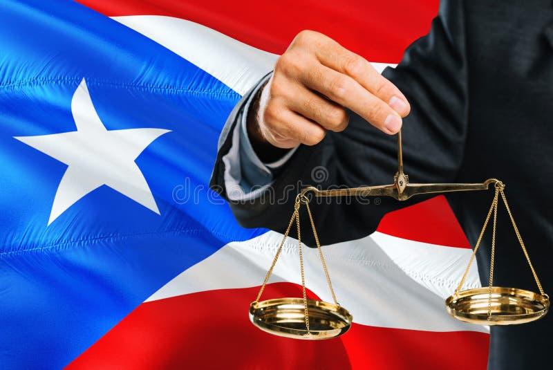 法官拿着正义金黄标度有波多黎各挥动的旗子背景 平等题材和法律概念 库存图片