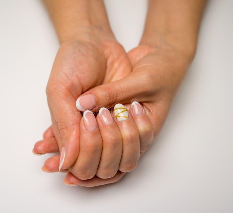 法式修剪和钉子胶凝体波兰语 有桃红色和白色指甲瓶的年轻,完善,修饰的妇女` s手 皇族释放例证