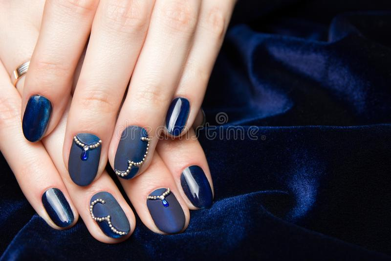 法式修剪-有蓝色修指甲的美好的被修剪的女性手与在深蓝背景的假钻石 免版税库存图片