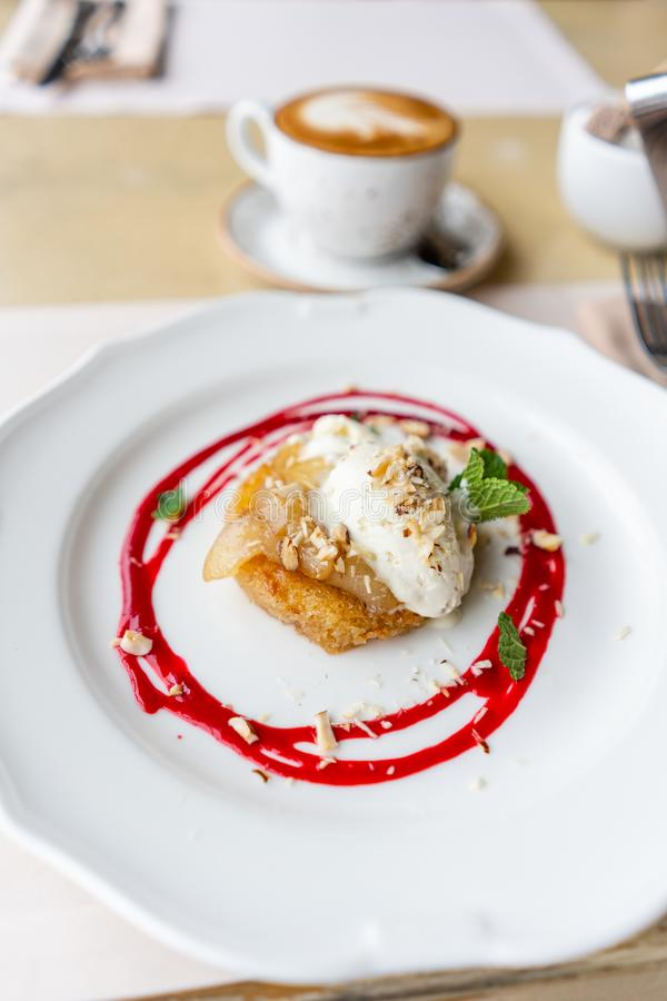 法式多士与香草冰淇淋、梨、坚果、薄荷的叶子和红色莓果调味汁的样式奶油蛋卷 清淡的早晨早餐 库存图片