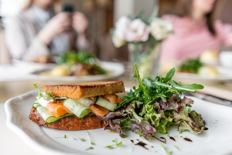 法式多士奶油蛋卷、三明治与三文鱼和黄瓜 清淡的早晨早餐,在桌上的新鲜的温暖的酥皮点心 库存图片