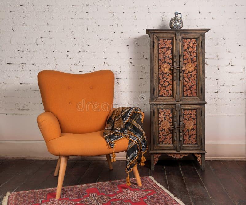 法式橙色翼背扶手椅、装饰精美的橱柜、白砖墙和格朗基木镶木地板 免版税库存照片