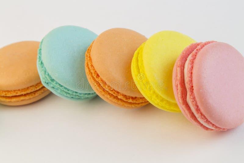 法式酥皮点心曲奇饼杯形蛋糕macarons特写镜头 在白色背景的蛋白杏仁饼干多颜色,黄色桃红色蓝色通心面 库存图片