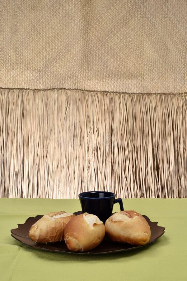 法式面包,在有黑杯子的板材在背景中 库存照片