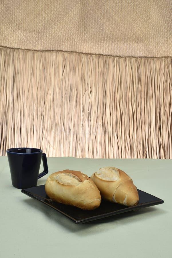 法式面包,在有黑杯子的板材在背景中 免版税库存图片