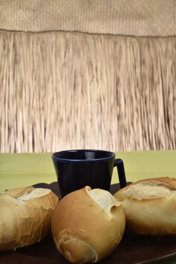 法式面包,在有黑杯子的板材在背景中 免版税库存照片