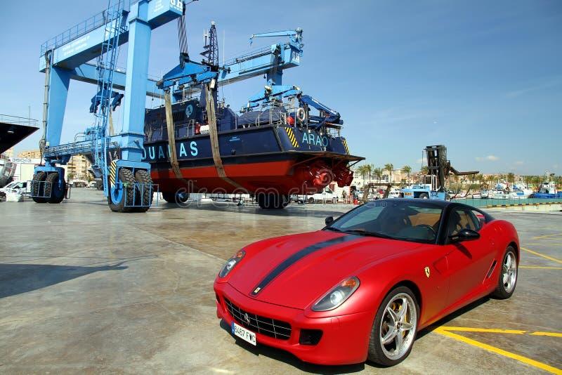 法拉利汽车和海岸警备队在一travelift在阿利坎特市 库存图片