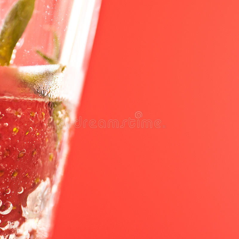 泡沫腾涌的玻璃浸没了草莓水 库存照片
