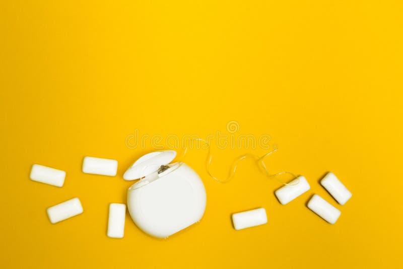 泡泡糖和牙线在黄色背景 文本的空间 免版税图库摄影