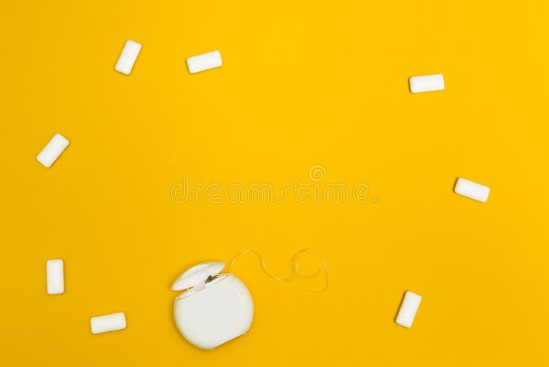 泡泡糖和牙线在黄色背景 文本的空间 免版税库存照片