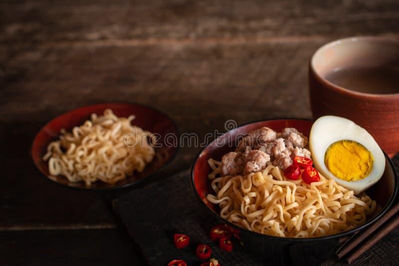 泡面用猪肉,鸡蛋和菜在黑碗在那里木桌上是辣椒,筷子,泡面在黑色 免版税库存图片