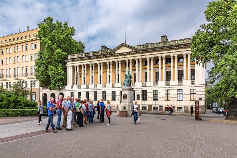 波兰波兹南9月11日2018观点的一个小组有指南的游人在中央图书馆buildin前面位于  免版税库存照片