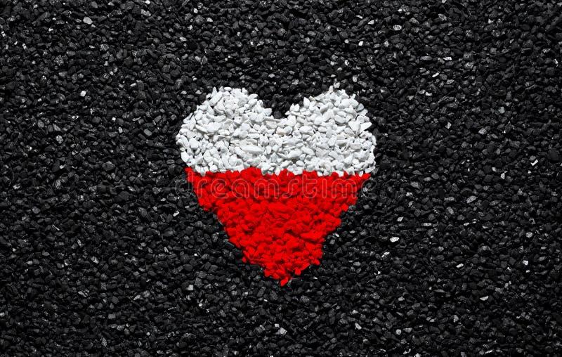 波兰的旗子,擦亮剂旗子、心脏在黑背景,石头、石渣和木瓦,墙纸 库存照片
