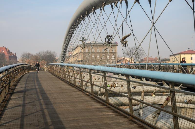 波兰,克拉科夫- 2018年11月:步行桥前Passerelle Ojca杂技演员Bernatka和雕塑对此的在陈列 免版税库存图片