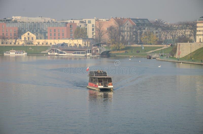 波兰,克拉科夫- 2018年11月:游人在维斯瓦河的一条小船乘坐在克拉科夫 图库摄影