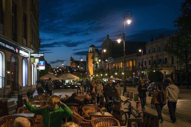 波兰-华沙- 09 05 2015 - 夜坐由街道的全景peoplae建设老镇 免版税图库摄影