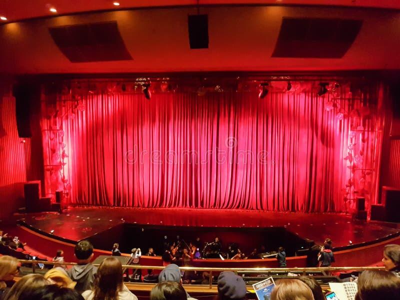 波哥大,哥伦比亚;2019å¹´4月13日:坐在colsubsidio剧院阶段的人们,在有红色帷幕的w el dorado街道附è 库存照片