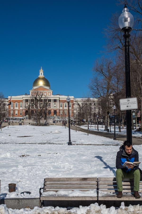 波士顿,麻省,美国,2016年2月,8日:栖息在室外长凳背面读书的年轻人在一个冷颤的积雪的公园 免版税库存照片