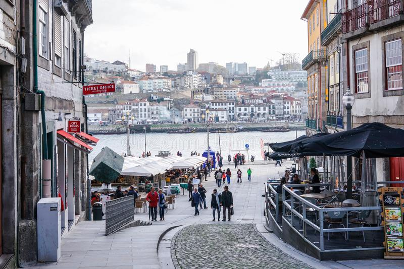波尔图,葡萄牙- 2018年12月:里贝拉广场日间,有人走和看法的向杜罗河河 库存图片