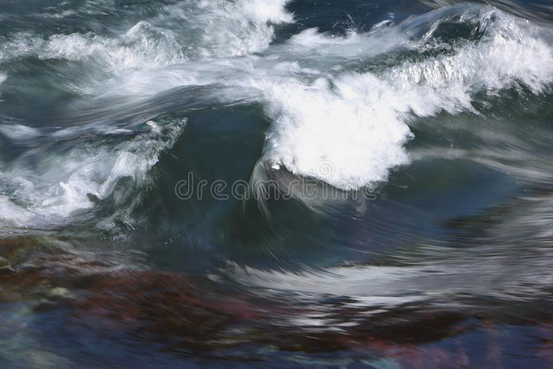 波浪冠在一条河的裂口的在春天 免版税库存图片