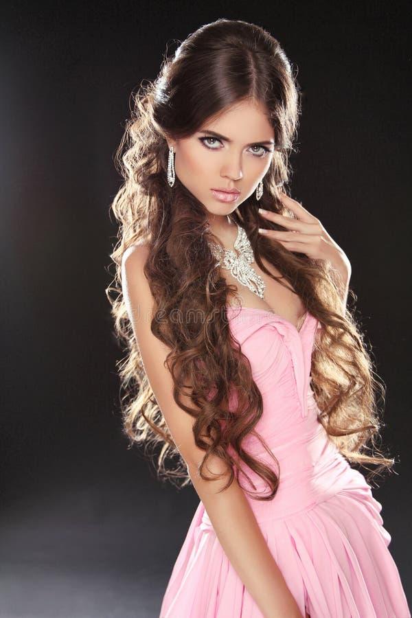 波浪发。桃红色礼服的美丽的性感的深色的妇女。健康 库存照片
